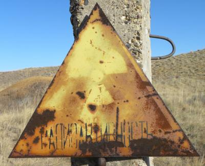 A faded radiation warning sign near a nuclear crater. Photo copyright Magdalena Stawkowski.