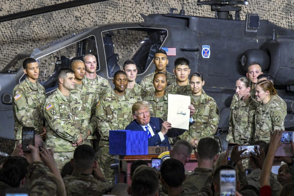 President Donald Trump poses with service members after signing the National Defense Authorization Act for Fiscal Year 2019 during a visit to Fort Drum, New York, on August 13, 2018.
