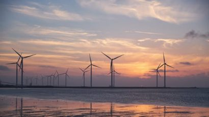 Wind turbines are pictured, along with water and a sunrise or sunset.