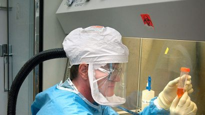 A CDC staff microbiologist examines reconstructed 1918 Pandemic Influenza Virus contained at a Biosafety Level 3-enhanced lab. Photo credit: Photo Credit: James Gathany/CDC