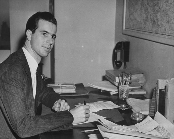 John Hersey at his desk, pen in hand, in the office at TIME. (Photo by Time Life Pictures/Pix Inc./The LIFE Picture Collection/Getty Images)