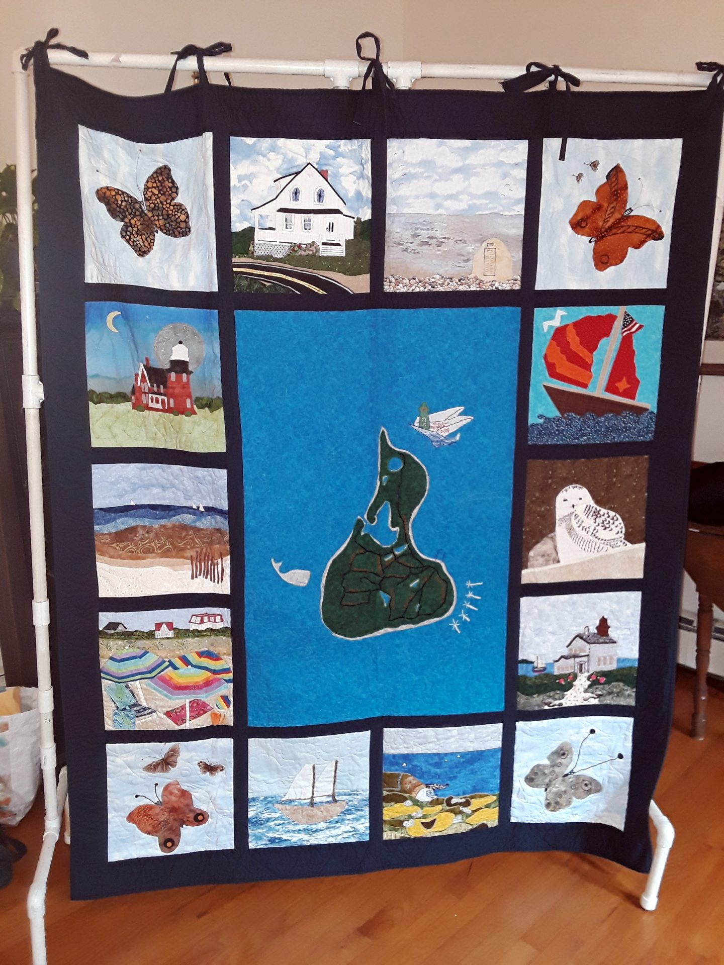Close up of a bed-sized quilt featuring Block Island. Note the five windmills at lower right. Image courtesy of Judy Mitchell.
