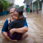 mother and child up to waist in floodwaters