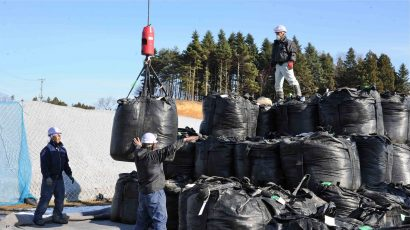 Workers stacking bags of soil.