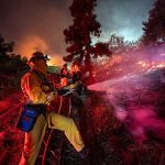 Firefighters work near the Getty Center in Los Angeles on October 28. Thousands of residents were forced to evacuate their homes after a fast-moving wildfire erupted.
