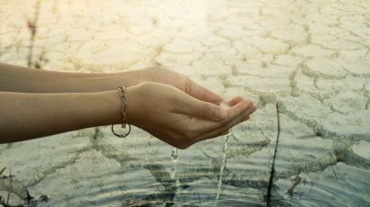 hands cupping water over cracked mud