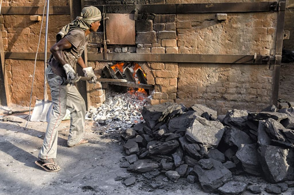 man shoving coal into oven in India