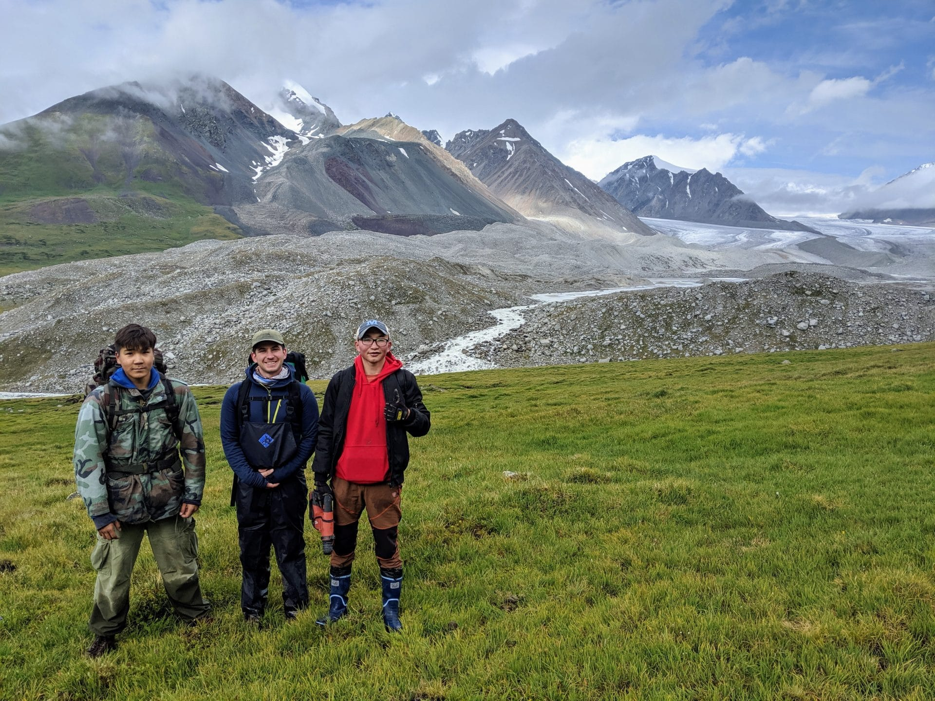 Team members Tumur Batbold, Peter Strand, and Oraza Seribol stand at the verdant edge of the Potanin glacier valley. The hills of tumbling rocks reveal young moraines.