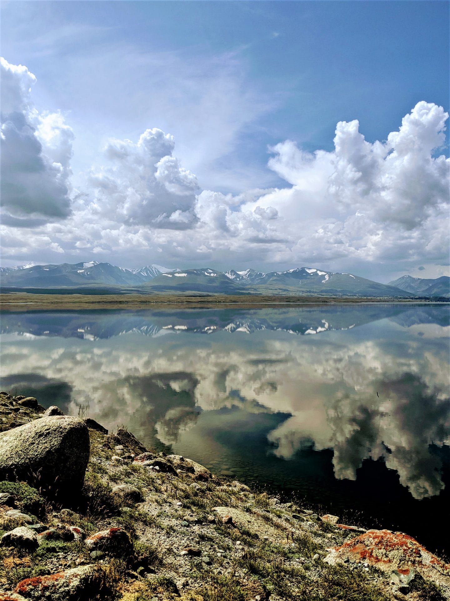 The Altai Mountains reflect off of Khurgan Nuur, a lake formed after the recession of glaciers thousands of years ago left a huge hollow that then filled with glacial melt.