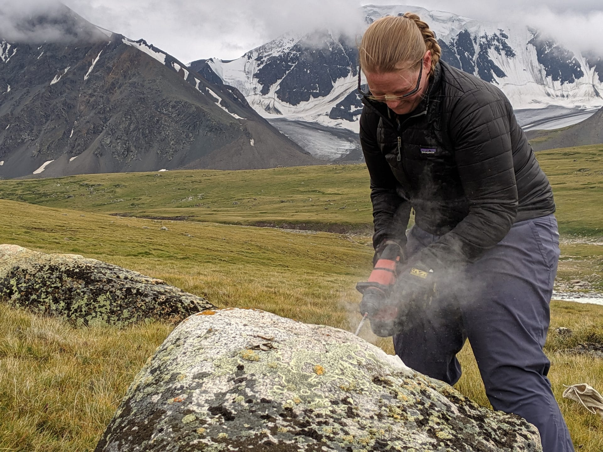 Jess Stevens drills into a deposited boulder. The rock chipping she gathers could hold the clue as to how fast the climate is warming.