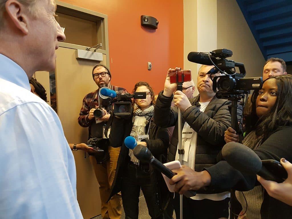 politician facing cameras and microphones
