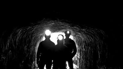 coal miner silhouettes lit by headlamps