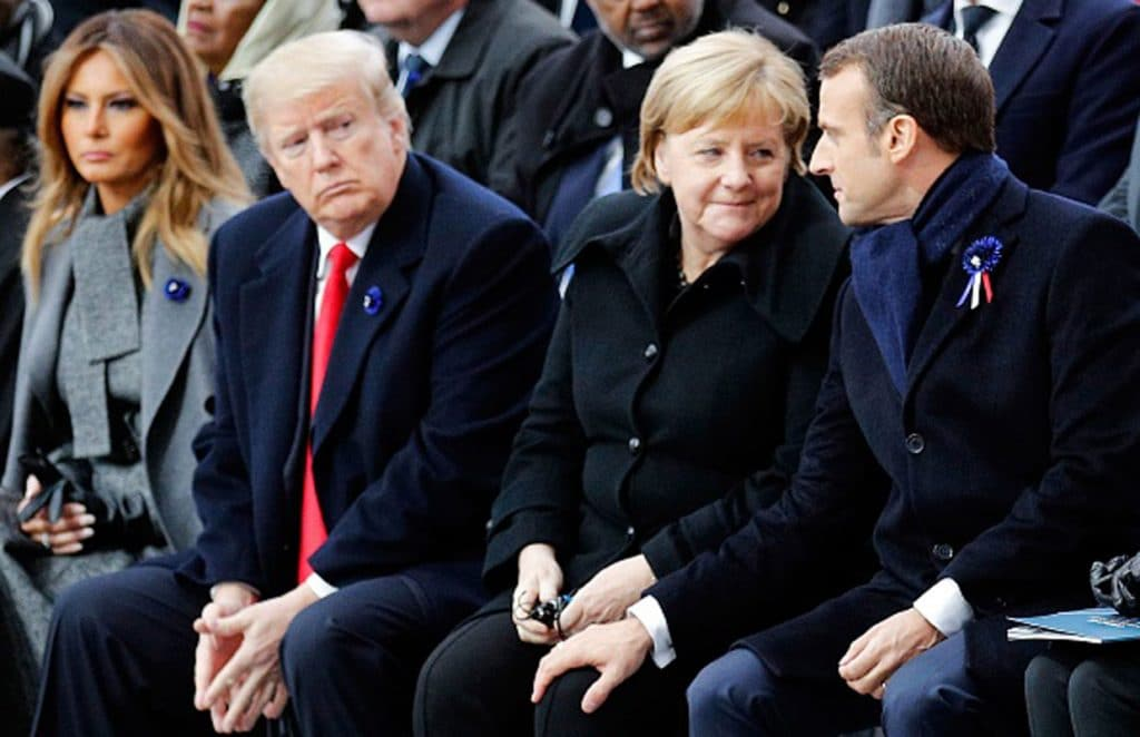 US President Donald Trump and his wife, Melania, look on as German Chancellor Angela Merkel communes with French President Emmanuel Macron during ceremonies commemorating the 100th anniversary of the end of World War I.