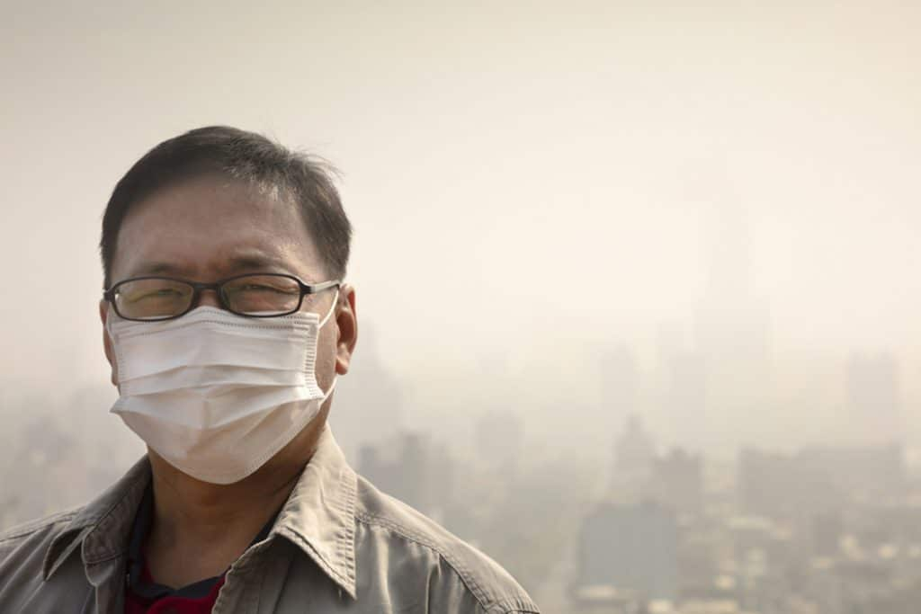 Man with face mask against hazy cityscape