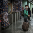 Passengers wait for the train with masks on.