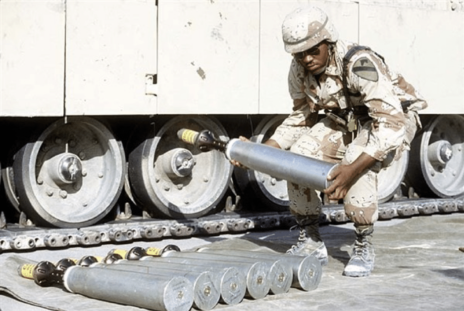 An ammunition specialist carries a 105 millimeter armor-piercing round to be used in an M-1 Abrams main battle tank during Operation Desert Shield in 1991. The object on the nose of the round is a sabot, a cover that protects and stabilizes the round's needle-like depleted uranium penetrator, then falls away as the projectile leaves the gun barrel. (Photo courtesy of the US Defense Department)
