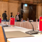A small Chinese flag placed in front of an empty chair.