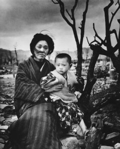 A mother and child, dressed in traditional clothing, sit on the ground amid rubble and burnt trees, Hiroshima, Japan, December 1945. On August 6, some four months previously, the United States had dropped an atomic bomb on the city--three days later a second one was dropped on Nagasaki. (Photo by Alfred Eisenstaedt/The LIFE Picture Collection via Getty Images)