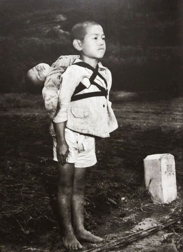 A barefoot boy waiting in line and staring ahead at a crematorium in Nagasaki, with his dead baby brother strapped to his back. Photo by US Marine photographer Joe O'Donnell