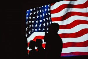 silhouettes of people in front of US flag