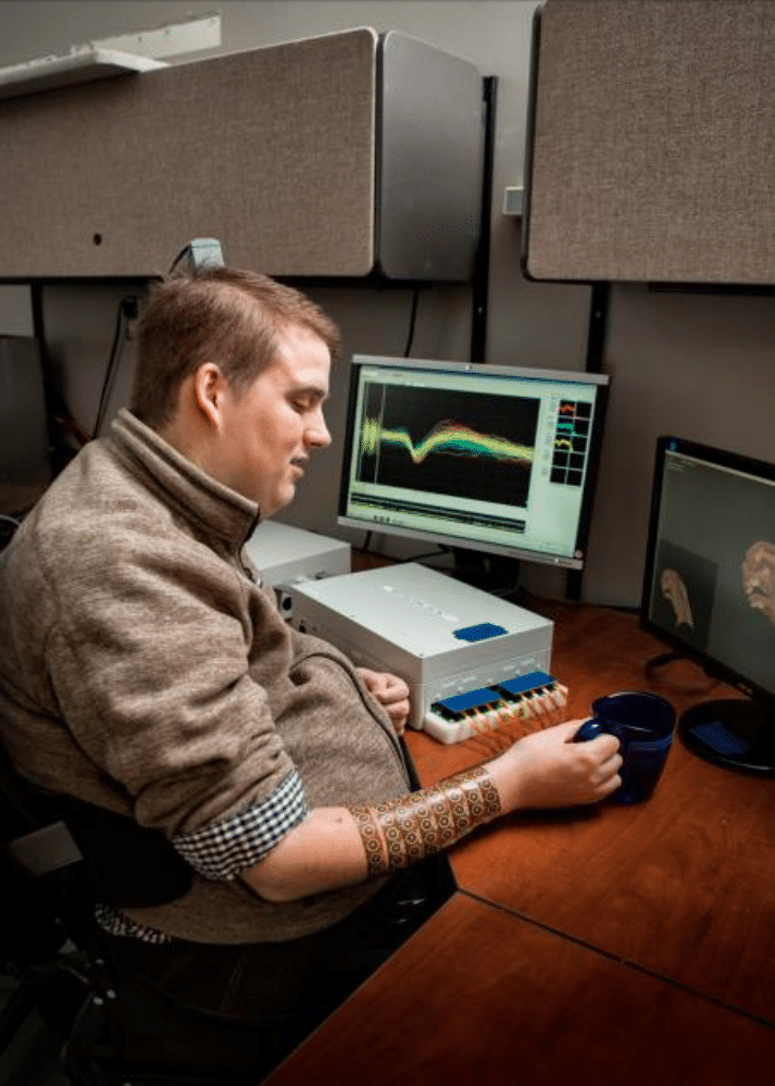 Signals from an implant in Ian Burkhart's brain are decoded by a computer then sent to a sleeve on his arm, activating muscles he is otherwise unable to control. (Battelle)