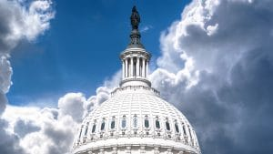 Capitol dome against blue sky white clouds