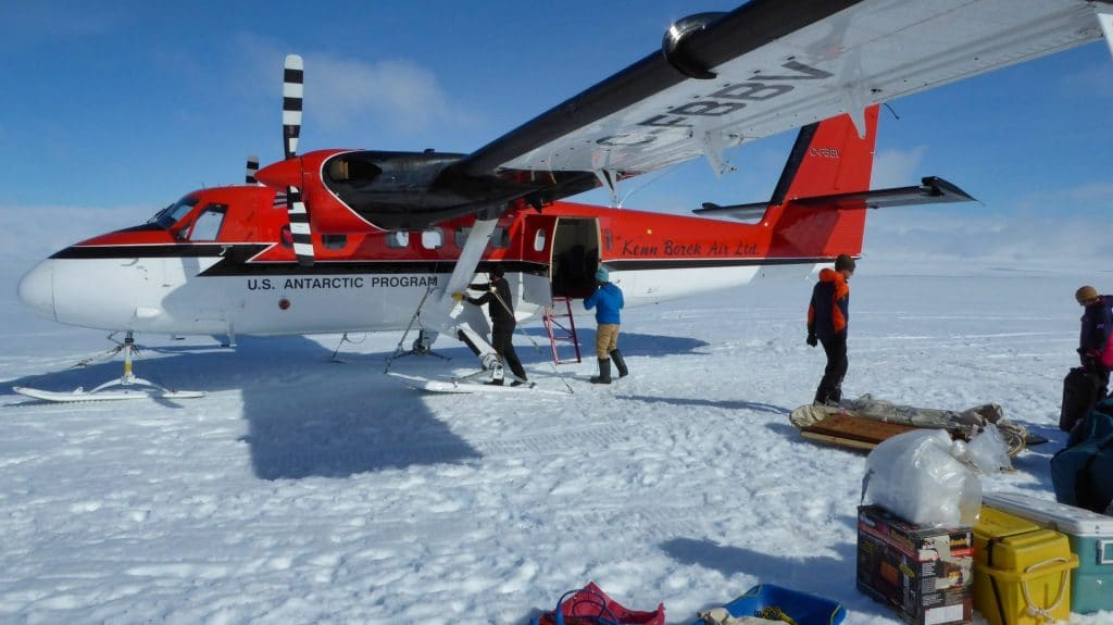 bright red-and-white plane on Antarctic ice