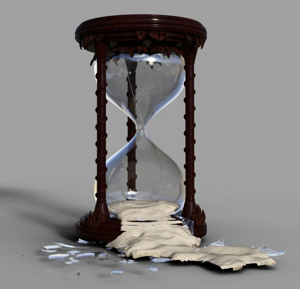 broken hourglass with sand pouring out