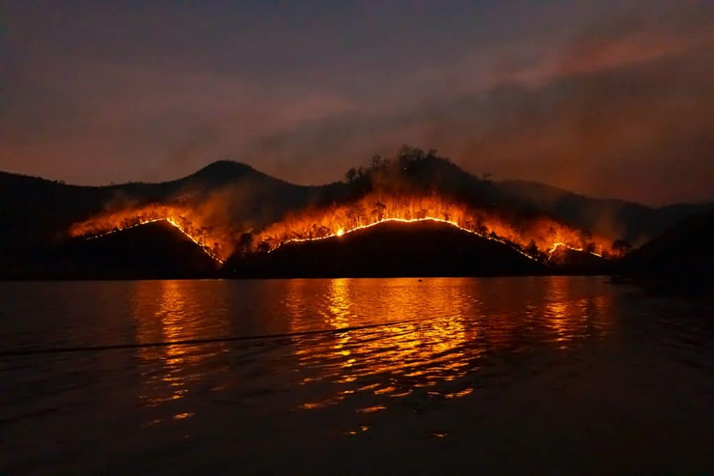 wildfire on mountain reflected in lake