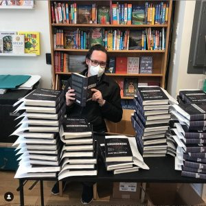 Alex Wellerstein (in a mask due to the COVID-19 pandemic) signs copies of his book, Restricted Data: The History of Nuclear Secrecy in the United States. Photo permission: Alex Wellerstein.