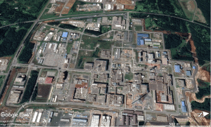 Figure 3. August 16, 2019 satellite image of the central area of Japan's $30-billion reprocessing and mixed-oxide-fuel production complex in Rokkasho Village, Japan. The white arrow shows the foundation hole for the mixed-oxide-fuel fabrication plant (Map Data: Google 2021 CNES/Airbus, Maxamar Technologies).