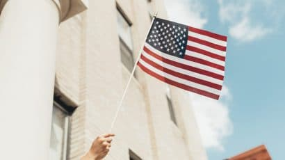 Hand waving American flag. Credit: Paul Weaver (@paulweaver). Image accessed via Unsplash. Unsplash License.