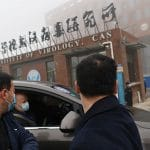 Members of the World Health Organization (WHO) team investigating the origins of the COVID-19 coronavirus arrive by car at the Wuhan Institute of Virology on February 3. (Photo by HECTOR RETAMAL/AFP via Getty Images)
