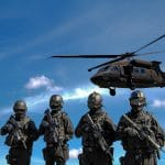 Four soldiers carrying rifles near helicopter under blue sky. Credit: Somchai Kongkamsri. Access via Pexels. Free to use.