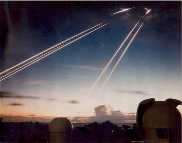 Time exposure showing the tracks of the missiles' six dummy warheads, white-hot from air friction, arriving 8,000 km down-range near Kwajalein Atoll in the Western Pacific. The domes in the foreground house tracking telescopes. As a part of the post-Cold War reductions, the Minuteman IIIs were downgraded to one warhead each. Credit: US Air Force photos from National Security Archive and US National Archive collections respectively. Public domain image.