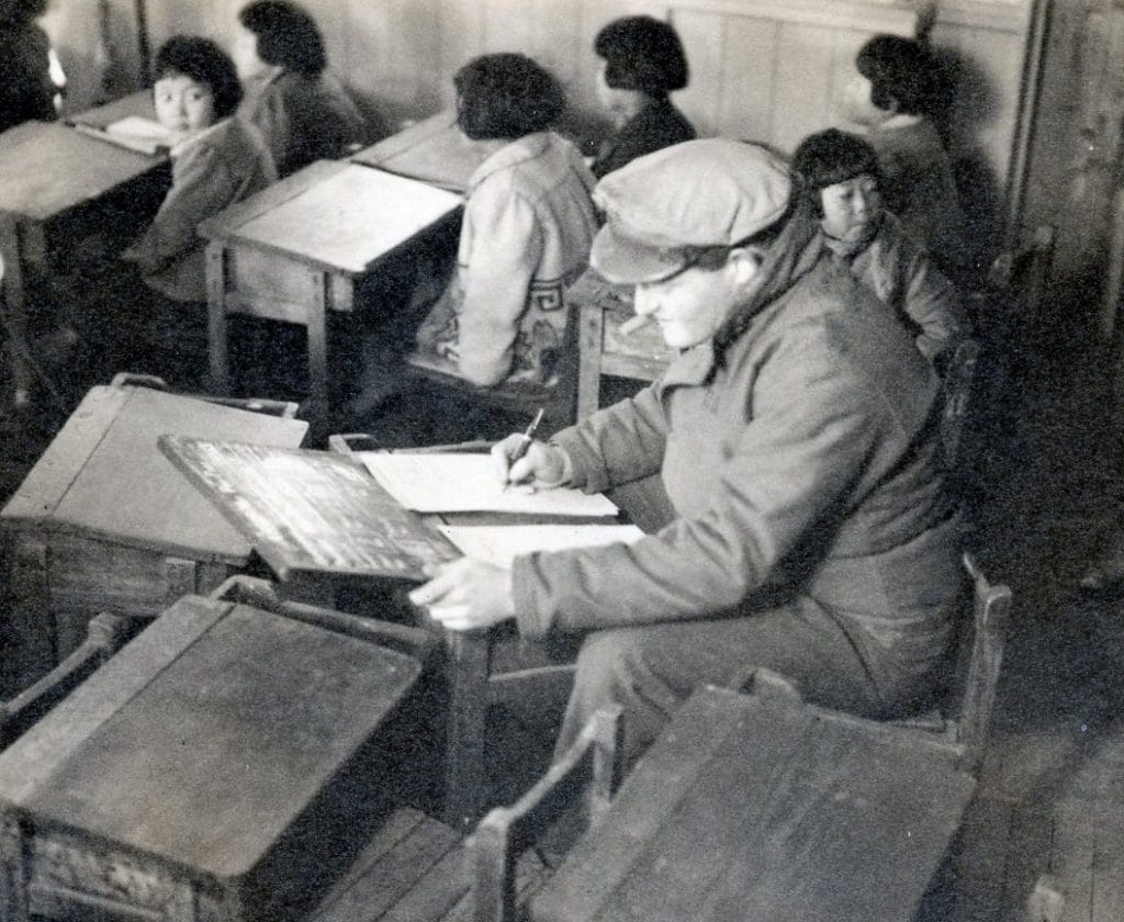 Herbert Sussan in a newly-reopened school room during filming in Nagasaki in 1946. (Credit: US Army)