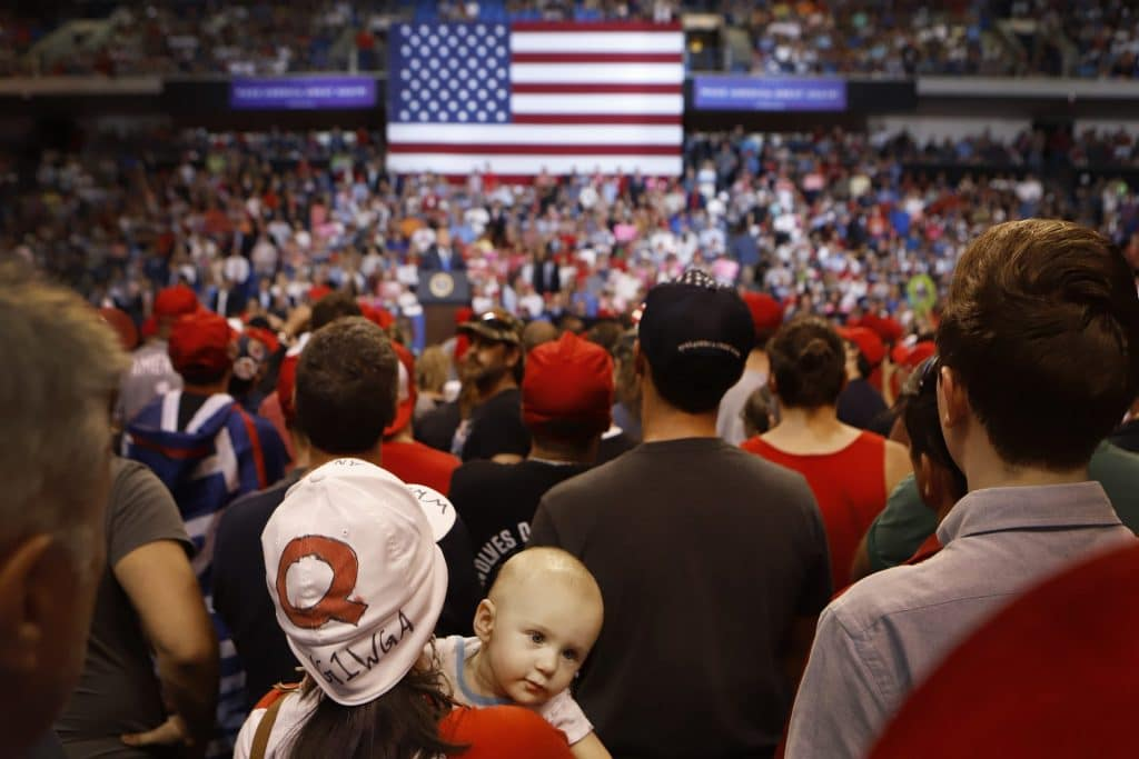 """A woman wearing a """"Q"""" hat with her son listens to President Trump speak to a large crowd in 2018 in Wilkes Barre, Penn. (Photo by Rick Loomis/Getty Images)"""