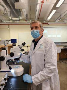 journalist wearing lab coat at microscope