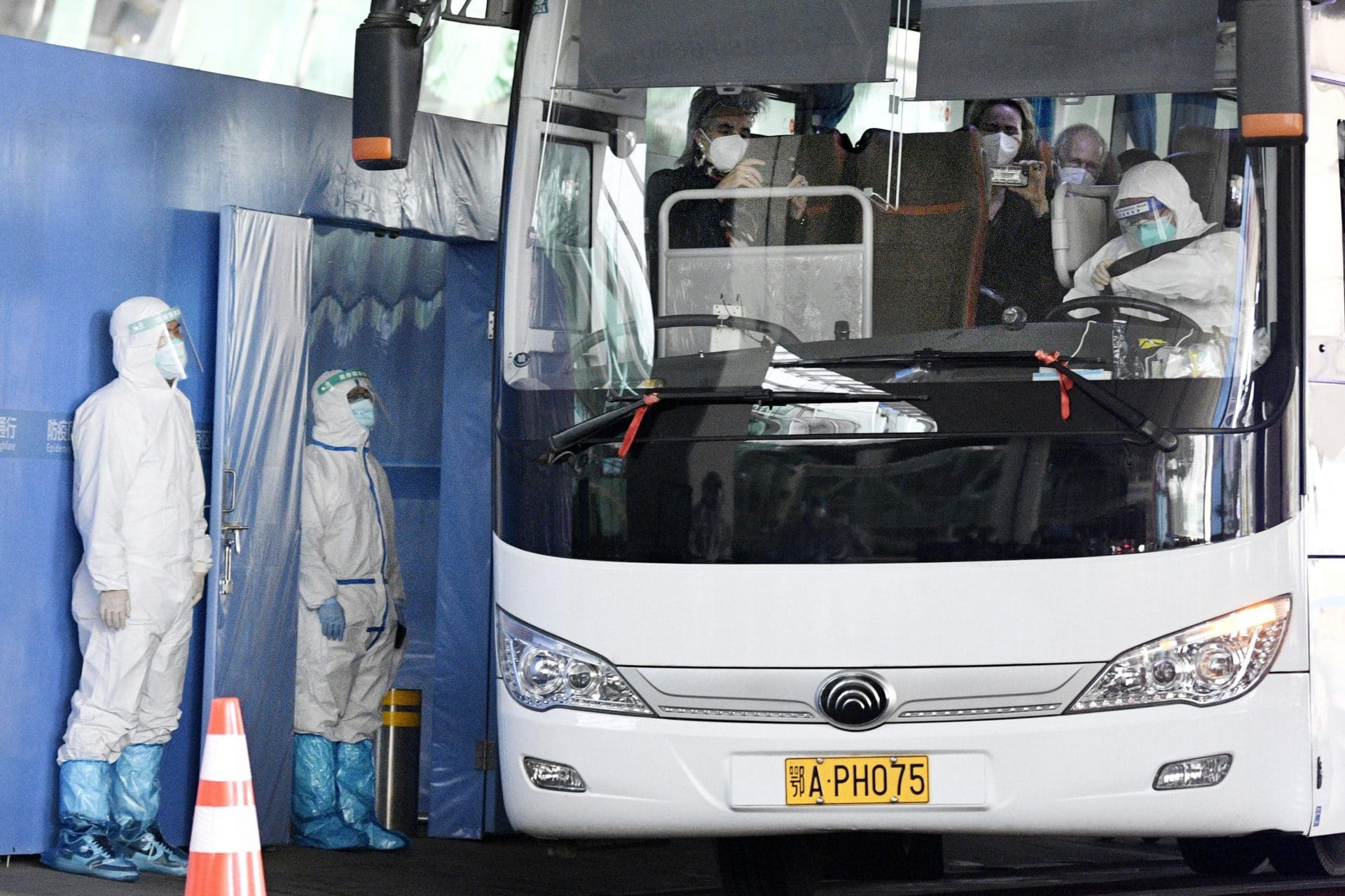 A bus carrying a team of experts from the World Health Organization departs an airport in Wuhan on Jan. 14, 2021, after arriving in the Chines