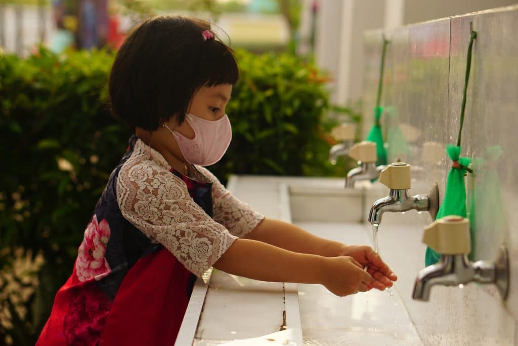 A girl washes her hands while wearing a mask. Credit: Pixabay.