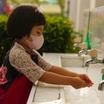 A girl washes her hands.