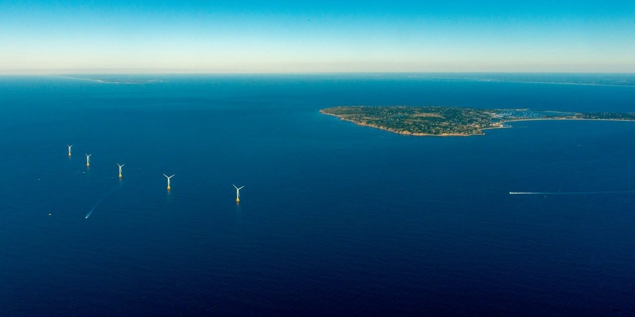 Looking west at Block Island from the air with its five offshore windmills, north is to the right in this aerial photo. The tip of Long Island can just be made out on the far left horizon; immediately behind Block Island on the right one can make out the line of white surf that marks the Connecticut shoreline. Image courtesy of Deepwater Wind.